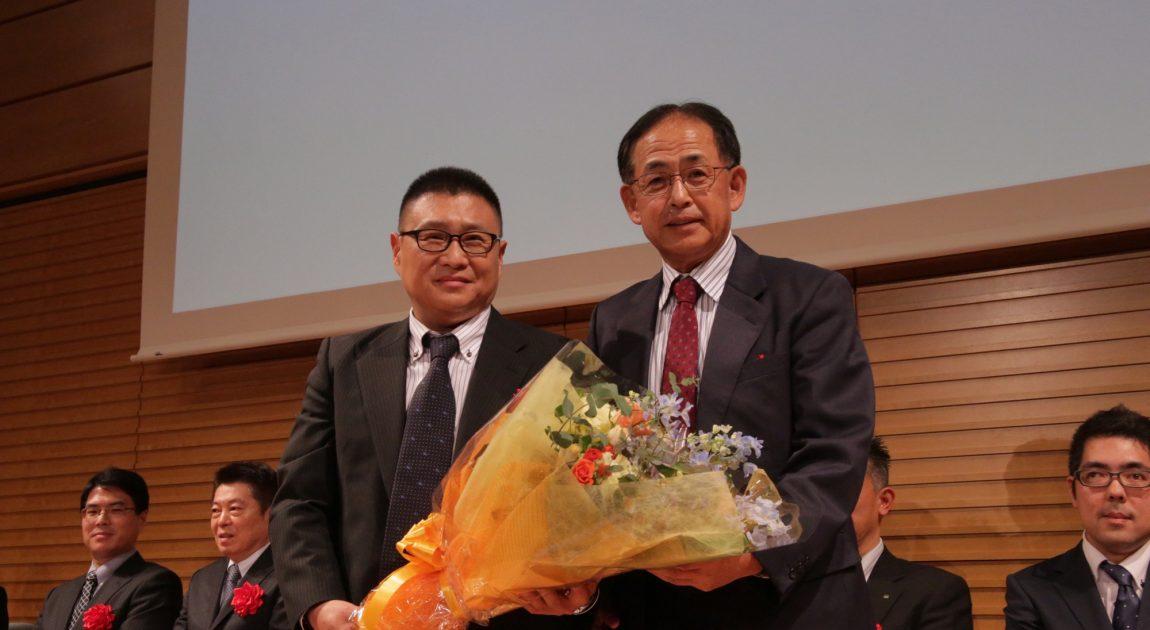 花束を持つ鈴木さんと下野代表理事