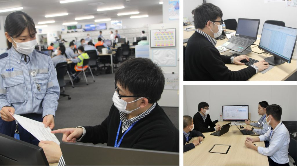 職場で同僚と資料を見ながら会話する熊川さん